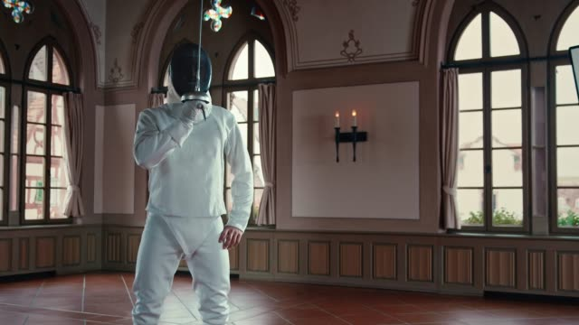 Male fencer lunging after saluting in castle