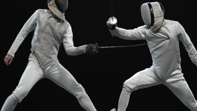 vídeos y material grabado en eventos de stock de el esgrimista slo mo macho puntúa un punto tocando el torso oponente con su arma - torso