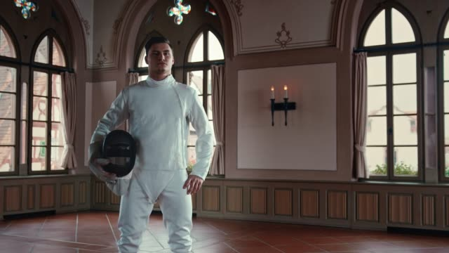 Male fencer wearing fencing mask in castle