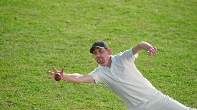 slo mo speed ramp male fielder catching the cricket ball in the sunny field - fielder stock videos & royalty-free footage