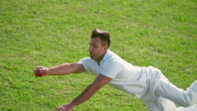 slo mo male fielder catching the cricket ball without gloves - fielder stock videos & royalty-free footage