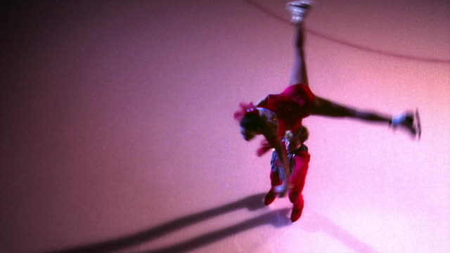 OVERHEAD male figure skater holding female skater over head + spinning / he puts her down