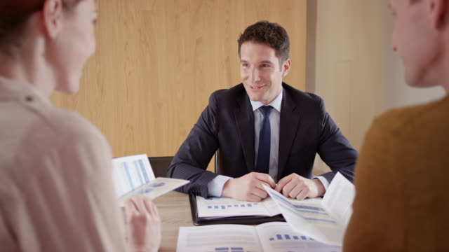 Male financial advisor shaking hands with a couple at a meeting in their home