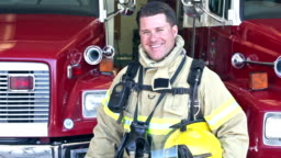 Male firefighter standing in front of fire engines