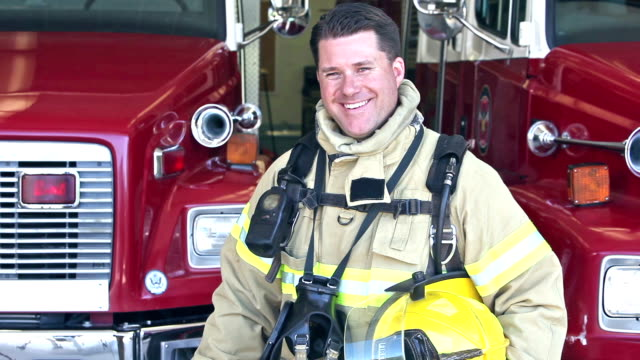 vídeos de stock e filmes b-roll de male firefighter standing in front of fire engines - bombeiro