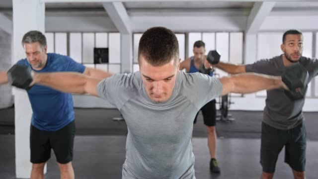 male fitness instructor leading a male class working out with weights in the fitness center - handsome people video stock e b–roll