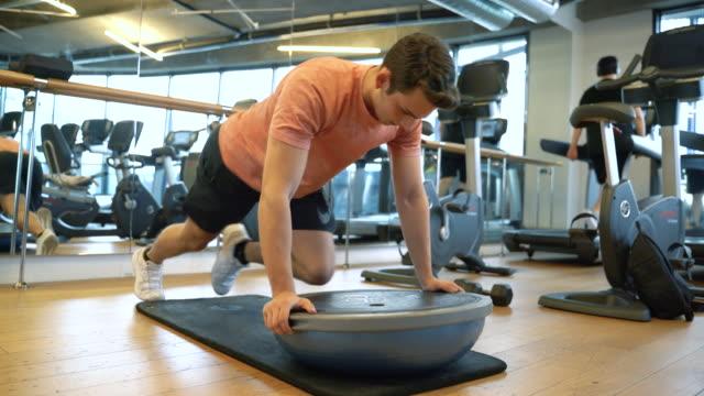 stockvideo's en b-roll-footage met mannelijke geschiktheidsinstructeur die met bosu saldobal uitwerkt - pilates