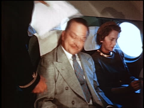 1950 male flight attendant putting pillow behind man's head on airliner / man next to woman