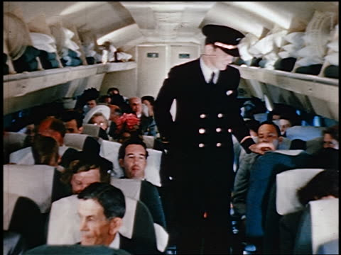 1950 male flight attendant talking to passengers + taking pillow from overhead bin on airliner - crew stock videos & royalty-free footage