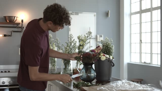male florist arranging flowers in vase at kitchen - fade in stock videos & royalty-free footage