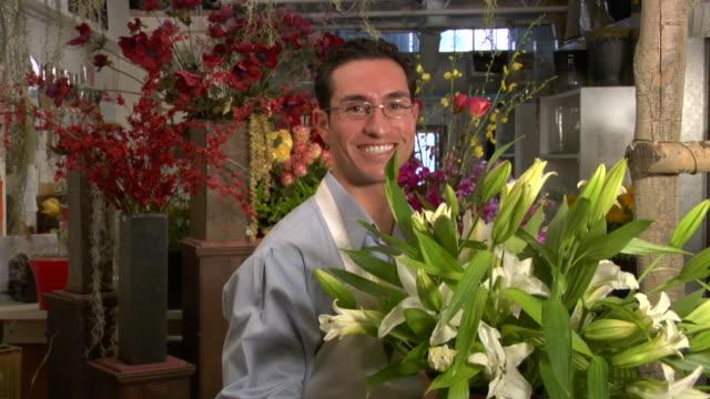 CU, Male florist holding bunch of lilies, portrait, Santa Fe, New Mexico, USA