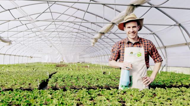 SLO-MO-DS männlichen Floristen Besprühen der Pflanzen im Gewächshaus