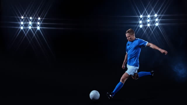 slo mo male football player in blue jersey kicking the ball on black background - top garment stock videos & royalty-free footage