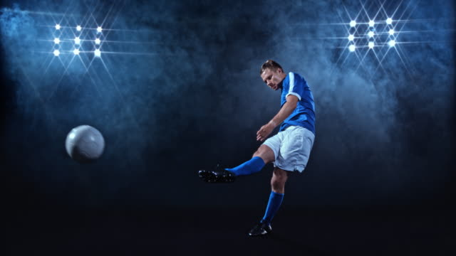 SLO MO Male football player in blue jersey kicking the ball on misty black background