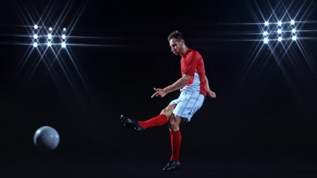slo mo ld male football player in red and white clothes kicking the ball on black background - black background stock videos & royalty-free footage
