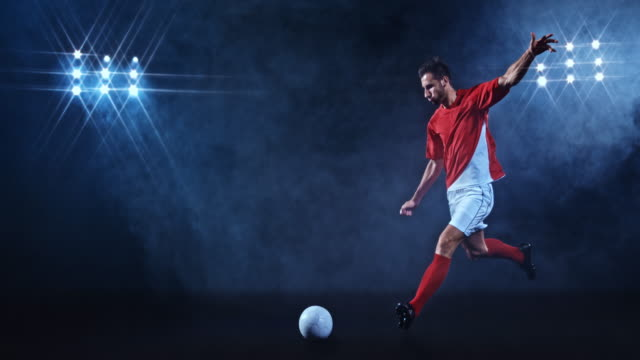 slo mo ld male football player in red and white outfit kicking the ball on misty black background - kicking stock videos & royalty-free footage