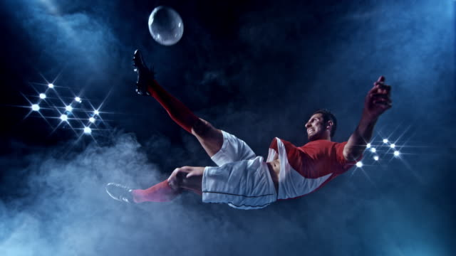 SLO MO LD Male football player kicking the ball in the air with a scissor kick on a black misty background