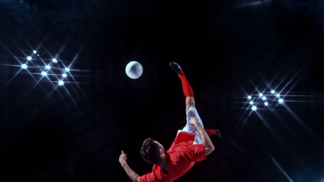 SLO MO LD Male football player kicking the ball with an overhead kick on a black background