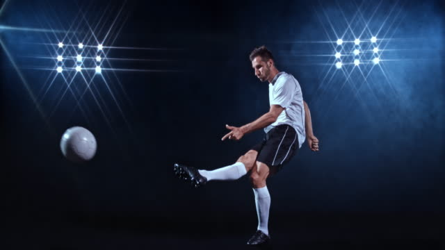 SLO MO LD Male footballer kicking the ball on black background