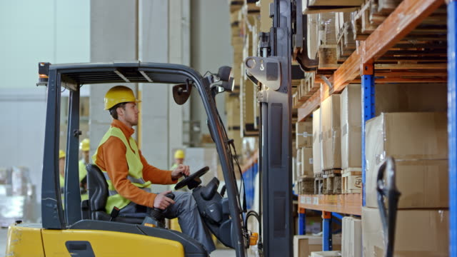 male forklift operator taking a pallet off a rack in the warehouse - deposito video stock e b–roll