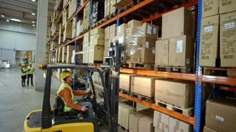cs male forklift operator taking a pallet off the rack in the warehouse - sachet stock videos & royalty-free footage