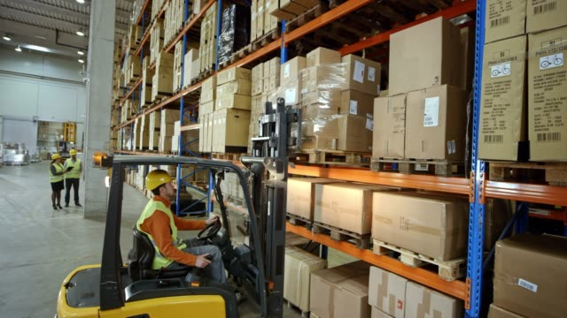 cs male forklift operator taking a pallet off the rack in the warehouse - forklift truck stock videos and b-roll footage