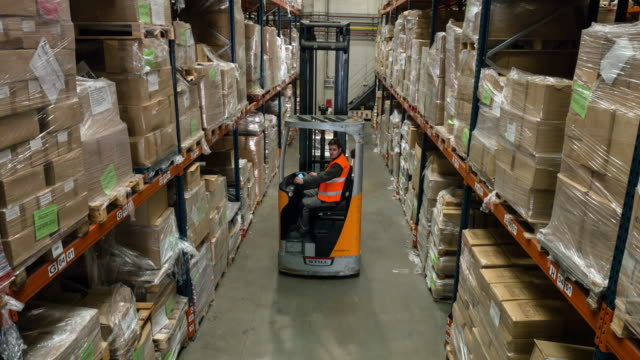 Male forklift truck driver working in distribution warehouse