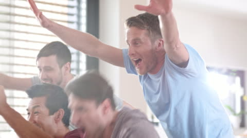 male friends celebrating the score in front of tv - male friendship stock videos & royalty-free footage