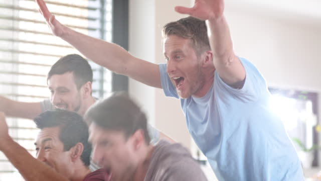 male friends celebrating the score in front of tv - exhilaration stock videos & royalty-free footage