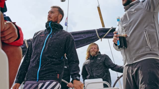 4K männlichen Freunden trinken Bier auf windigen und regnerischen Segelboot, Real-time
