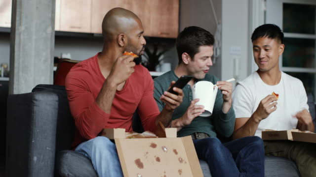 male friends eating different takeout meals together - fast food stock videos and b-roll footage