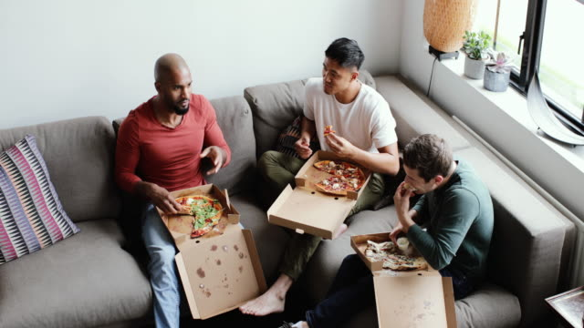 vidéos et rushes de male friends eating takeout pizza in an apartment - amitié masculine