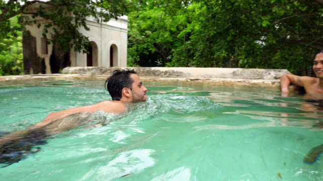 ms male friends hanging out in pool at luxury tropical resort - zen like stock videos & royalty-free footage