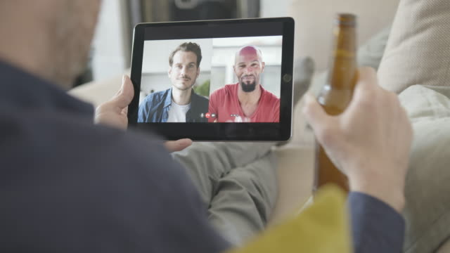 male friends having video call with drinks from home using video conferencing technology during social distancing lock down during covid-19 - happy hour video stock e b–roll