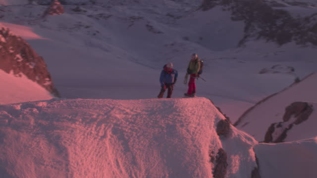 male friends hiking on snow covered ridge - mountain climbing stock videos & royalty-free footage