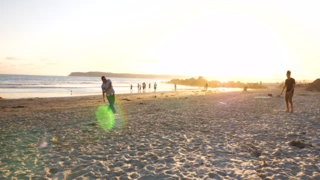 ws male friends kicking soccer ball on beach at sunset - pacific islander stock videos & royalty-free footage