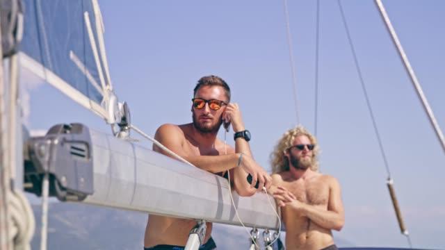 Männliche Freunde anhören von Musik mit Kopfhörern auf sonnigen Segelboot, Real-time