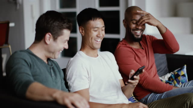 vídeos de stock e filmes b-roll de male friends looking at smartphone together - film moving image