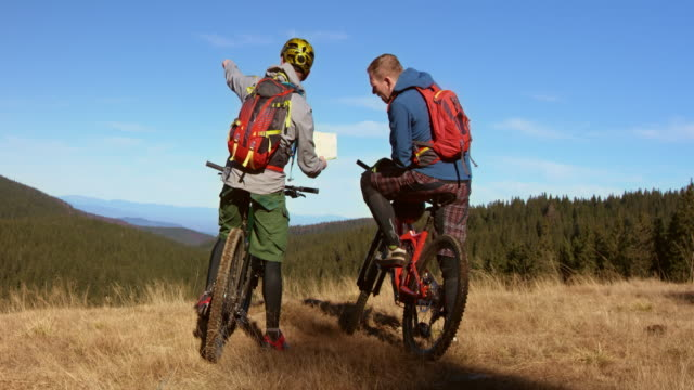 Male friends on mountain bikes discussing the right trail on a map