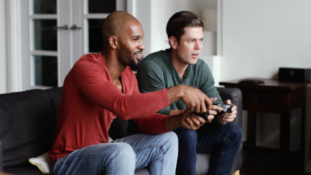 vídeos de stock, filmes e b-roll de male friends playing on a games console together - male friendship