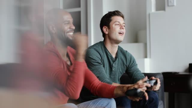 vídeos de stock, filmes e b-roll de male friends playing on a games console - male friendship