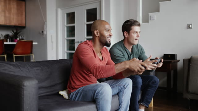 male friends playing on a games console - adult stock videos & royalty-free footage