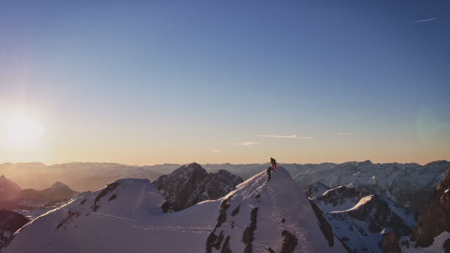 male friends reaching mountaintop during sunrise - austria stock videos & royalty-free footage