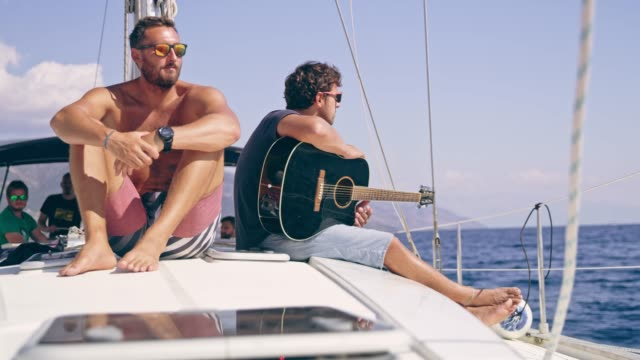 male friends relaxing, playing guitar on sunny sailboat, real time - yachting stock videos & royalty-free footage