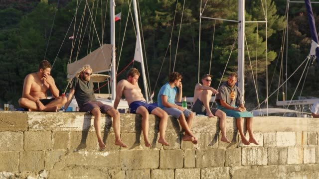 male friends relaxing, sitting on rock wall at marina, real time - 30 39 years stock videos & royalty-free footage