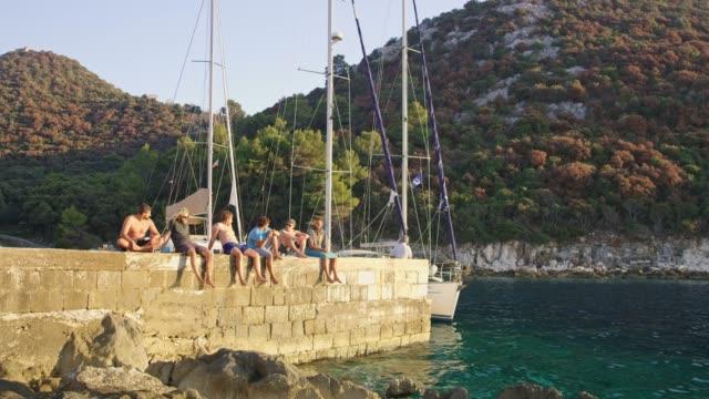 vídeos de stock e filmes b-roll de male friends relaxing, sitting on rock wall over ocean, real time - pier