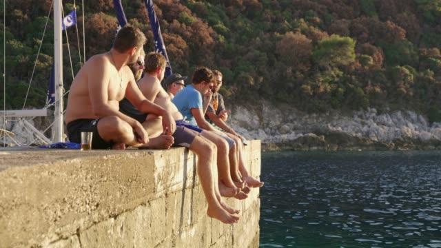 Amis de sexe masculin de détente, assis sur le mur de roche sur océan, temps réel