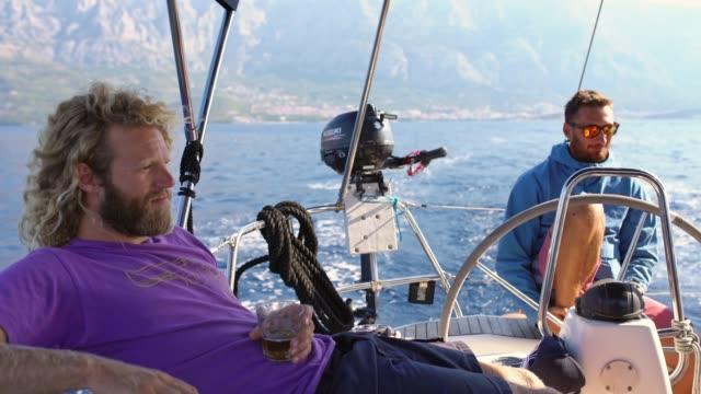 4k männlichen freunden auf segelboot segeln, relaxen und biertrinken, real-time - segelmannschaft stock-videos und b-roll-filmmaterial