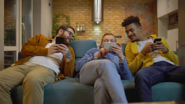 Male friends sitting on couch with gadgets, talking having fun with mobile apps