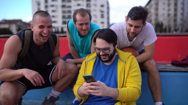 male friends sitting on stands after playing basketball - large stock videos & royalty-free footage